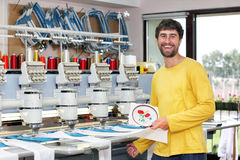 Happy operator of automatic embroidery machines. Happy smiling operator of automatic embroidery machines  working at his workplace Royalty Free Stock Photos
