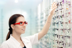 Happy Optician Choosing Between Eyeglasses Frames. Young female optometrist in optics shop reaching for glasses Royalty Free Stock Photos