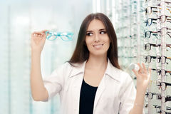 Happy Optician Choosing between Glasses and Contact Lenses. Female optometrist proposing eyeglasses and contacts as options Royalty Free Stock Photography