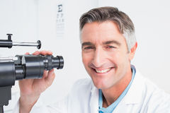 Happy optician using slit lamp in clinic Royalty Free Stock Photo