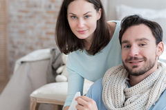Happy optimistic couple looking at you. We are together. Nice joyful optimistic couple sitting at home and looking at you while recovering from cold Stock Images