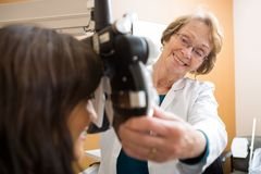 Happy Optometrist Adjusting Phoropter For Patient Royalty Free Stock Image