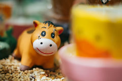 Happy orange cow clay doll on the gravel Royalty Free Stock Photography