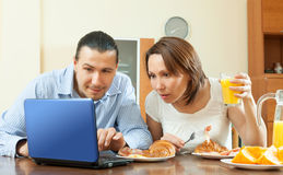 Happy ordinary couple using laptop during breakfast Stock Photography