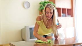 Happy ordinary woman cleaning table