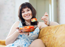 Happy ordinary woman eats vegetables Royalty Free Stock Photos