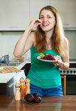 Happy ordinary woman in green eating  beets Royalty Free Stock Photography