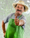 Happy organic farmer with a green apron shows his upraised thumb Royalty Free Stock Photo