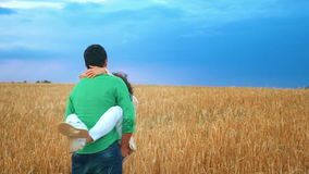 Happy сouple having fun outdoors in wheat field over sunset. Laughing Joyful Family together. Slow motion stock video footage
