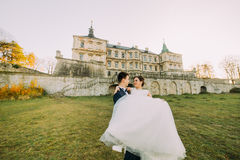The happy outdoor portrait of the groom carrying the bride at the background of the old-fashioned castle. Royalty Free Stock Image
