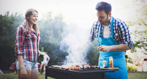 Happy outgoing people enjoying bbq. And grilling meat royalty free stock photos