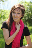 Happy outside. Beautiful young brunette with pink scarf smiles outdoors royalty free stock photos