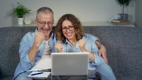 A happy middle-aged couple, excited to win online on a laptop.