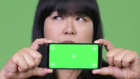 Happy overweight Asian woman thinking while showing phone. Studio shot of beautiful overweight Asian woman against chroma key with green background stock video footage