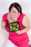 Happy overweight woman eating a salad Royalty Free Stock Photos