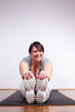 Happy overweight woman exercising/stretching Stock Photography
