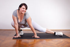Happy overweight woman exercising/stretching Stock Image
