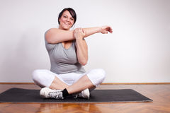 Happy overweight woman exercising/stretching Royalty Free Stock Image