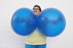 Happy Overweight Woman Holding Exercise Balls Stock Photo