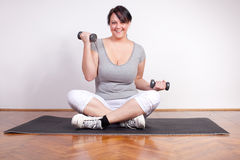 Happy overweight woman lifting weights Stock Photos