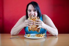 Happy overweight woman stuffing herself Stock Image