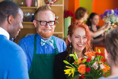 Happy owner of flower shop with staff and customer Royalty Free Stock Photos