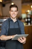 Happy Owner Holding Digital Tablet In Cafe. Portrait of happy male owner holding digital tablet while standing in cafe Stock Photography