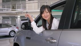 Happy owner of new auto, smiling consumer asian female shows keys sitting in salon and peeking through window at. Car dealership stock footage