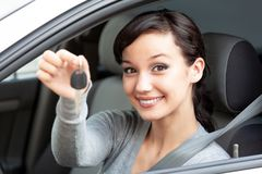 Happy owner of a new car is showing the car key. Royalty Free Stock Photo