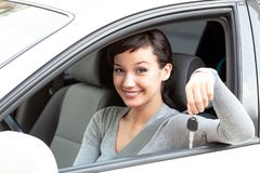 Happy owner of a new car is showing the car key. Stock Photo