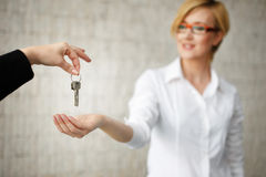 Happy owner passing keys from house in office Stock Photo