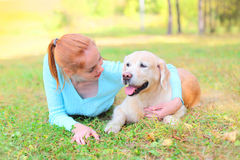 Happy owner woman and Golden Retriever dog lying on gras Stock Photos