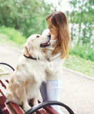Happy owner woman and Golden Retriever dog sitting on the bench Stock Photo