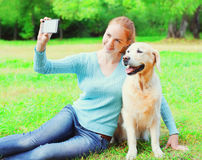 Happy owner woman with Golden Retriever dog is taking picture selfie portrait on a smartphone on summer day. Happy owner woman with Golden Retriever dog is Royalty Free Stock Photo