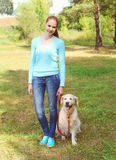 Happy owner woman and Golden Retriever dog walking in summer Stock Image