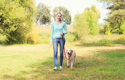 Happy owner woman and Golden Retriever dog walking together in park