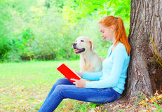Happy owner woman is reading a book with Golden Retriever dog sitting near tree in the park Royalty Free Stock Images