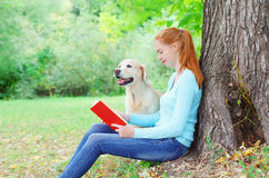 Happy owner woman reading book with Golden Retriever dog sitting in park Royalty Free Stock Images