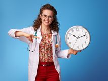 Happy paediatrician doctor pointing at clock on blue Stock Photo
