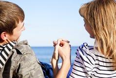Happy pair on coast behind blue sea Stock Photo