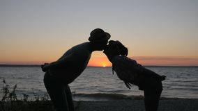 Happy pair Kisses to Embankment river on background sunset, kiss of Lovers to coast river in sundown,. Embrace of young couple on summer shore sea, romantic stock footage