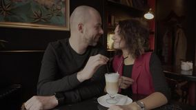 Happy pair of newlyweds sitting in a cafe and drinking a latte from one cup. stock video footage