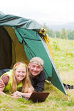 Happy pair in tent works on a laptop Stock Photos