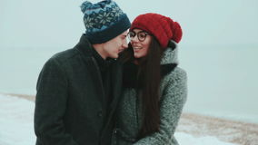 Happy pair, on warm clothes, walk outside on coast sea, behind gray sky. Couple walking on beach holding hands stock footage