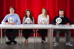 Panel Judges Holding 10 Score Signs. Happy Panel Judges Sitting In Front Of Red Curtain Showing 10 Score Signs royalty free stock photography