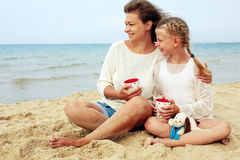 Happy parent and child drinking tea on the beach. Portrait of a happy parent and child drinking tea on the beach royalty free stock photography