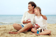 Happy parent and child drinking tea on the beach. Portrait of a happy parent and child drinking tea on the beach stock photos