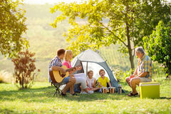 Happy parent and children enjoying camping Stock Image