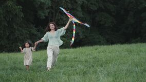 Happy mother and daughter walking with kite on lawn