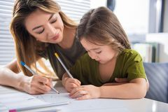 Happy parent and kid painting picture at home. Lets draw our family. Cheerful mother and daughter are creating image together on paper. Woman is embracing child Stock Photo